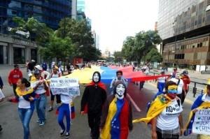 Manifestantes de la oposición marchan con el rostro cubierto.